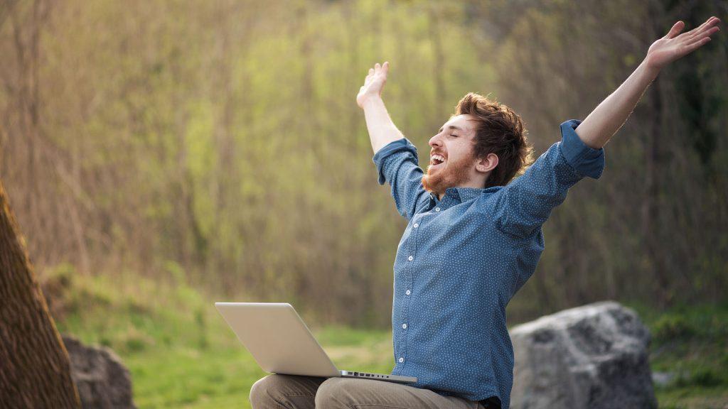 Mann som sitter med en laptop og holder hendene i været